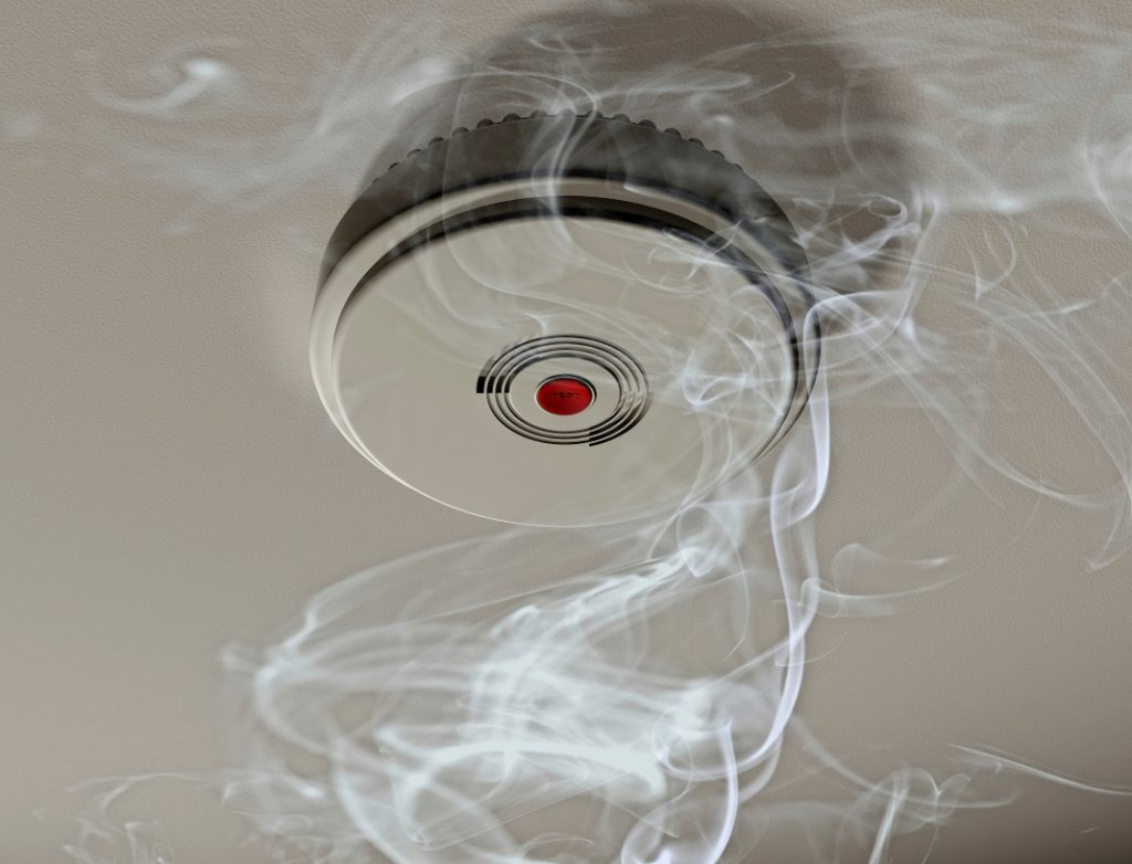 Illustration of a smoke alarm sounding off in a smoky room